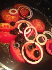 Luomumunista pyöräytetty auringonkeltainen munakas saa lisäväriä tomaatista, punasipulista ja oliiveista.